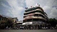 Motorcyclists drive past commercial buildings in Hanoi. Photo credit: Brent Lewin/Bloomberg