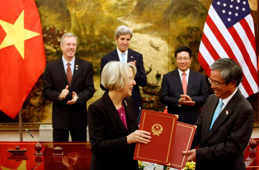 US Peace Corps Director Carolyn Hessler Radelet (L, front) and Vietnamese ambassador to the US Pham Quang Vinh (R) exchange document after signing a document on Peace Corps Operation in Vietnam at the Government Guesthouse as part of the visit by US President Barack Obama in Hanoi, May 24, 2016. Photo: Kham/Reuters
