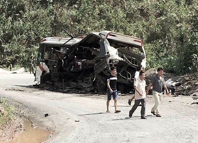 Men pass the site where a vehicle carrying a group of Vietnamese people from Thakhek Town in central Laos to Vietnam's Nghe An Province suddenly exploded at around 4 a.m. on June 2, 2016. Photo credit: Zing