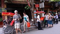 Foreign tourists walk around the ancient quarter of Hanoi in a file photo. The quarters, which attracts many tourists, contains mostly traditional Vietnamese 'tunnel houses', which are of a long and narrow construction. Photo credit: Hoang Dinh Nam/AFP