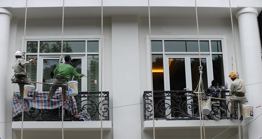 Workers paint the facade of a newly built hotel in downtown Hanoi on January 7, 2015. Photo credit: Hoang Dinh Nam/AFP