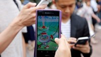 """Men play the augmented reality mobile game """"Pokemon GO"""" on their mobile phone near a busy crossing in Shibuya district in Tokyo, Japan, July 22, 2016. Photo credit: Reuters"""