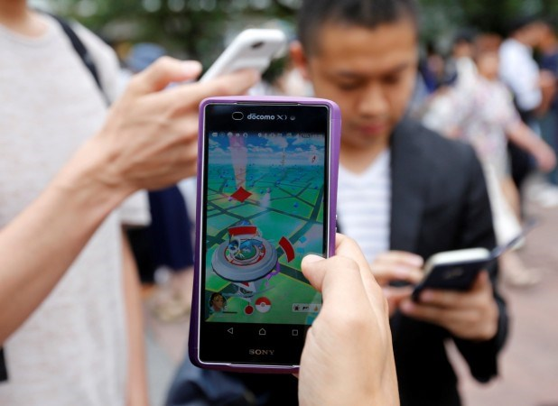 "Men play the augmented reality mobile game ""Pokemon GO"" on their mobile phone near a busy crossing in Shibuya district in Tokyo, Japan, July 22, 2016. Photo credit: Reuters"
