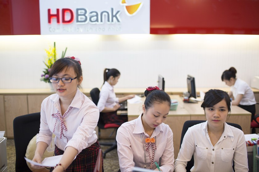 Employees work behind a counter inside an HDBank branch in Ho Chi Minh City in a file photo. Photo credit: Brent Lewin/Bloomberg