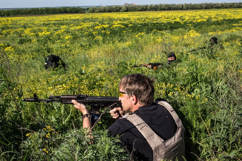 Members of the Donbass Battalion, a pro-Ukraine militia, take cover after shots were fired at a Ukrainian military checkpoint in Dobropillya, Ukraine.