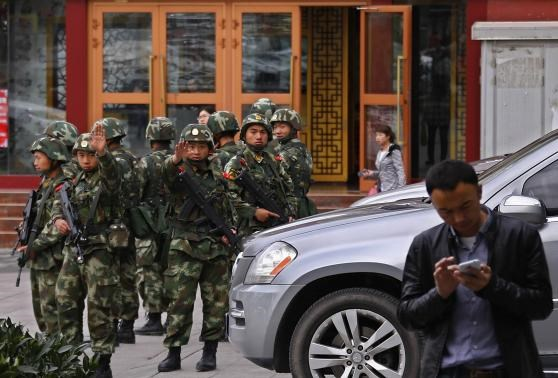 Paramilitary policemen gesture to stop a photographer from taking pictures as they stand guard after an explosives attack hit downtown Urumqi on Thursday, Xinjiang Uighur Autonomous Region May 23, 2014.