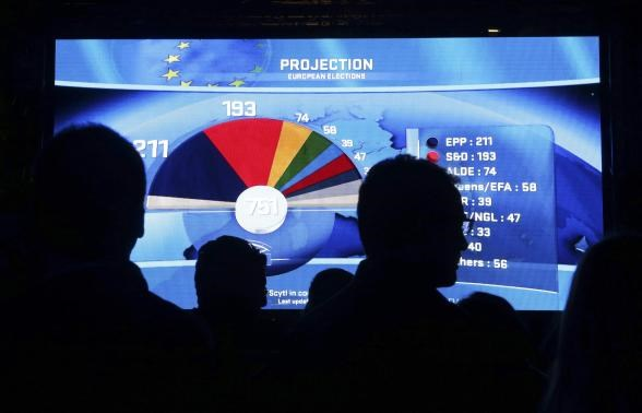 People watch a board displaying provisional results of the European Parliament election at the EU Parliament in Brussels May 25, 2014. May 25, 2014.