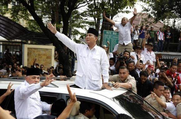 Indonesian presidential candidate Prabowo Subianto (C) and his vice presidential running mate Hatta Rajasa wave to supporters after registering at the Election Commission for the upcoming July 9 election in Jakarta May 20, 2014.