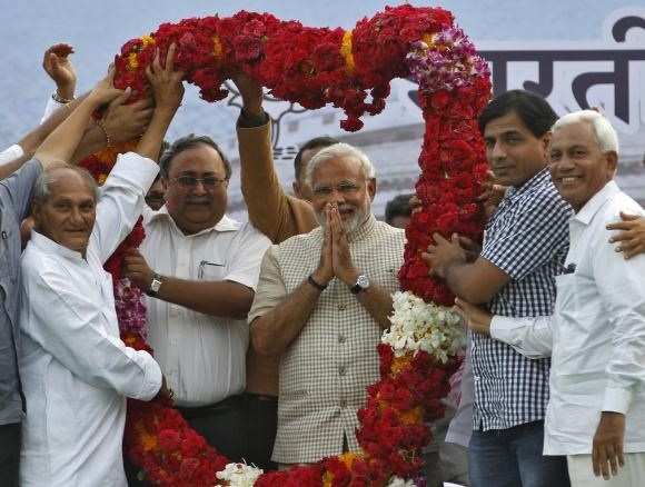 Hindu nationalist Narendra Modi, the prime ministerial candidate for India's main opposition Bharatiya Janata Party (BJP), gestures as he receives a garland from his supporters during a public meeting in Vadodara, in the western Indian state of Gujarat, M
