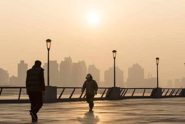 People walk at The Bund as heavy smog engulfs Shanghai, on Dec. 25, 2013.