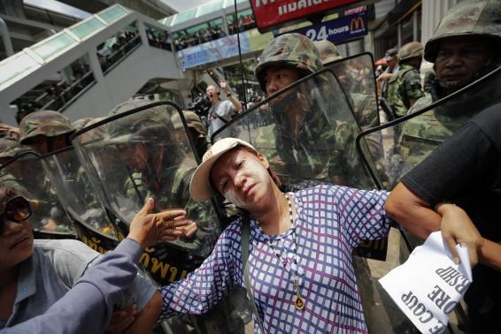 Protesters against military rule push against the shields of soldiers deployed to control them at Bangkok's shopping district May 25, 2014.