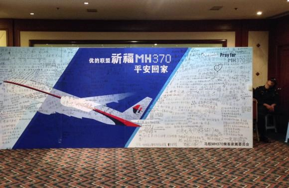 A policeman takes a nap beside a board written with messages for passengers onboard the missing Malaysia Airlines Flight MH370 during a closed meeting held between Malaysian representatives and Chinese relatives of passengers on Flight MH370 at Lido Hotel