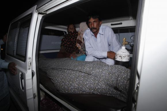 Mohammad Iqbal sits next to his wife Farzana's body, who was killed by family members, in an ambulance outside of a morgue in Lahore May 27, 2014.