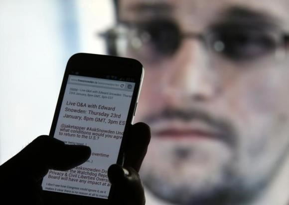 A man uses his cell phone to read updates about former U.S. spy agency contractor Edward Snowden answering users' questions on Twitter in this photo illustration, in Sarajevo, January 23, 2014.