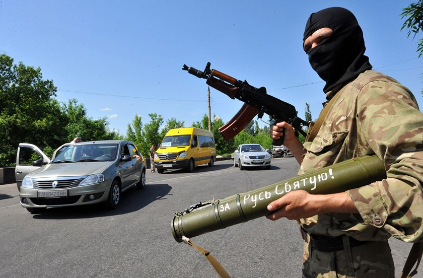 An armed pro-Russian miltiant holds a gun as he checks passing cars near the eastern Ukrainian city of Kramatorsk on May 20, 2014. Rebels have established city strongholds, and often move from town to town -- if they're not killed or captured in firefight