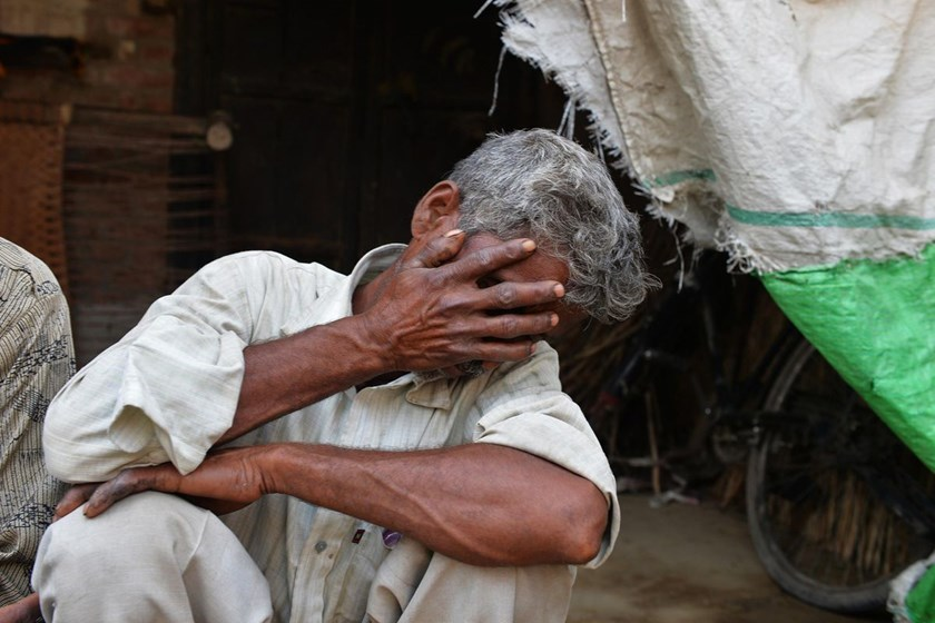 The father of one of the gang-rape victims covers his face as he mourns in Katra Shahadatgunj in Badaun, India's Uttar Pradesh state, on May 31, 2014. Photo credit: AFP
