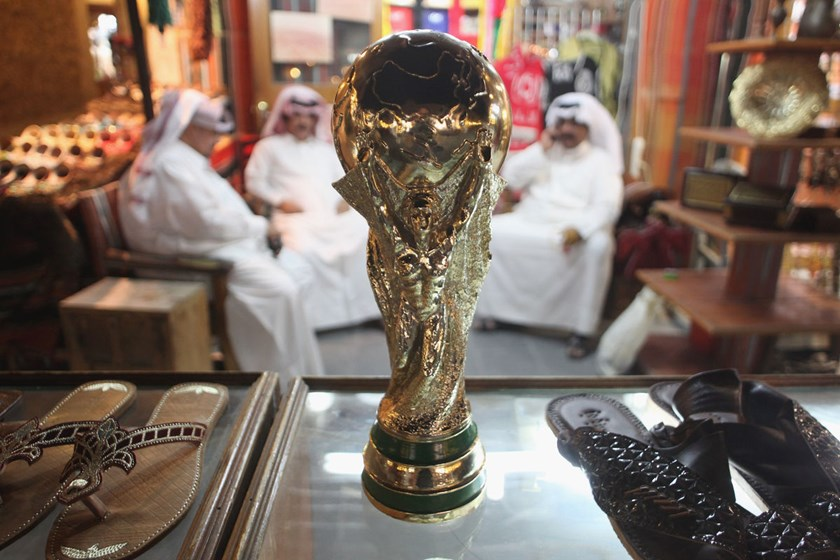 Men sit at a shoemaker's stall with a replica of the FIFA World Cup trophy in the Souq Waqif traditional market in Doha, Qatar.