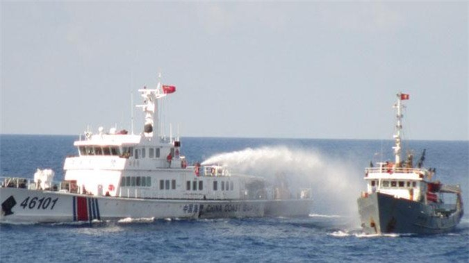 A Chinese coast guard ship, left, shoots water cannon at a Vietnamese vessel