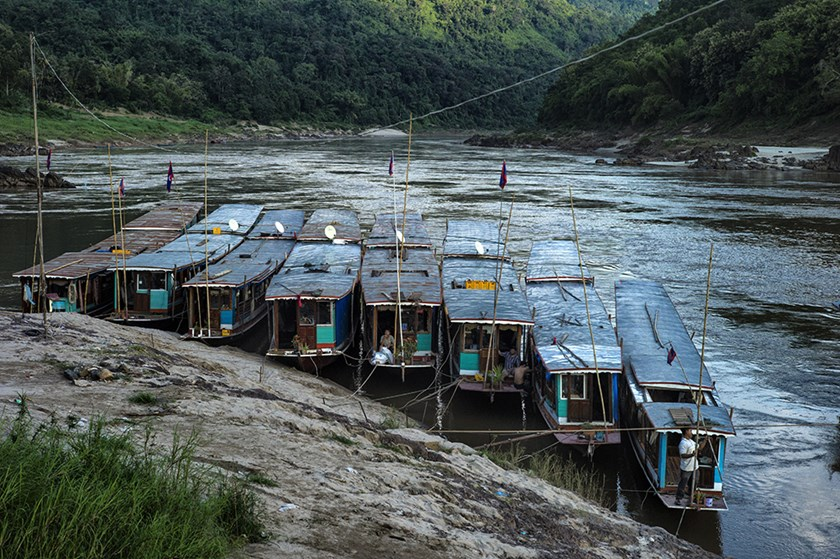 At a makeshift port on the Mekong river in Northern Laos, traditional wooden boats at mooring for the night. Photograph: Roland Neveu/LightRocket via Getty Images