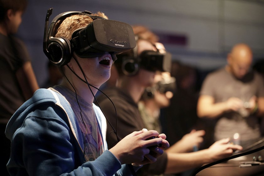 Gamers wear high-definition virtual reality (VR) headsets, manufactured by Oculus VR Inc., as they a play video game during the Eurogamer Expo 2013 in London. Oculus raised $2.4 million on Kickstarter in 2012 for the development of its virtual-reality gam