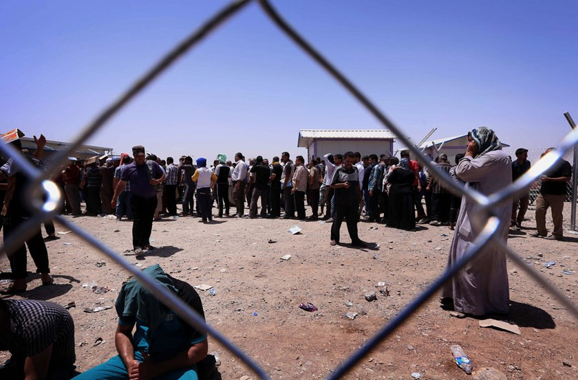 Iraqi families fleeing violence gather at a checkpoint in Aski kalak in the autonomous Kurdistan region, on June 10, 2014. Photo credit: AFP