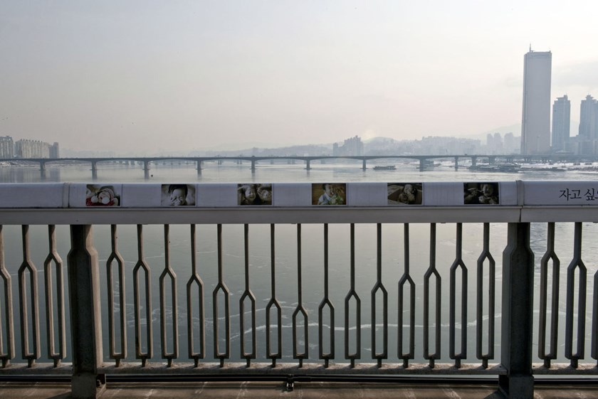 Pictures of children are displayed along the railing of the Mapo Bridge to dissuade potential suicides, in Seoul, South Korea. Photo credit: AFP