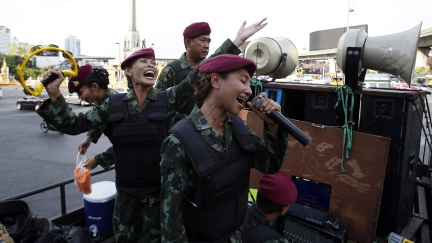 Female Thai soldiers sing patriotic songs on a military truck as soldiers and police take positions to prevent demonstrations against military rule. Photo credit: Reuters