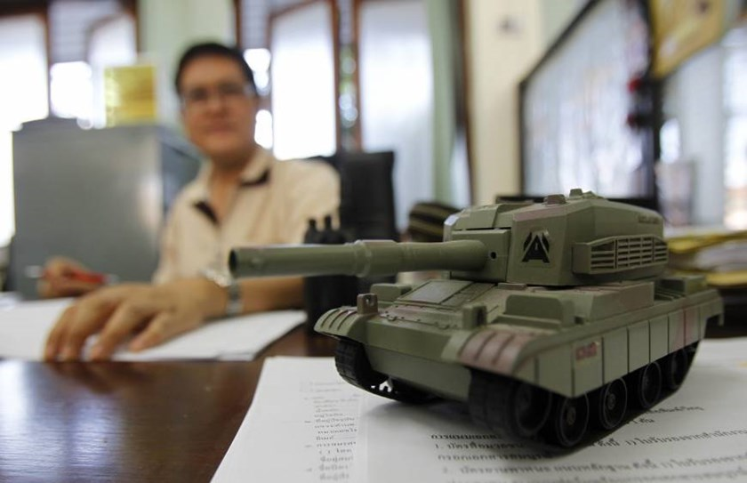 A toy tank is seen on the desk of an official as he works at Government House, after it reopened following a military coup in Bangkok. Photo credit: Reuters