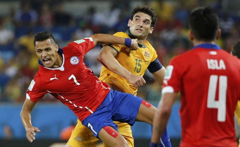 Chile's Alexis Sanchez (7) reacts near Australia's Mile Jedinak (centre) during their World Cup Group B match at the Pantanal arena in Cuiaba June 13, 2014.