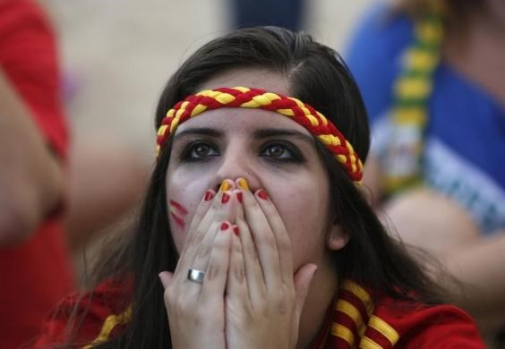 A Spanish fan reacts as she watches the 2014 World Cup soccer match between Netherlands and Spain on a large screen at Copacabana beach in Rio de Janeiro.