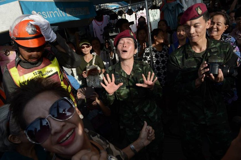 Thai soldiers dance with residents at a military event organized to 'return happiness to the people' at Bangkok's Victory Monument, the site of recent anti-coup rallies, in early June. Photo credit: AFP