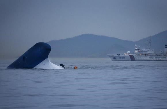 A Coast Guard ship passes near the upturned South Korean ferry ''Sewol'' in the sea off Jindo April 16, 2014.