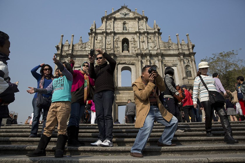Tourists take photographs in front of the Ruins of St. Paul's Cathedral in Macau, China.