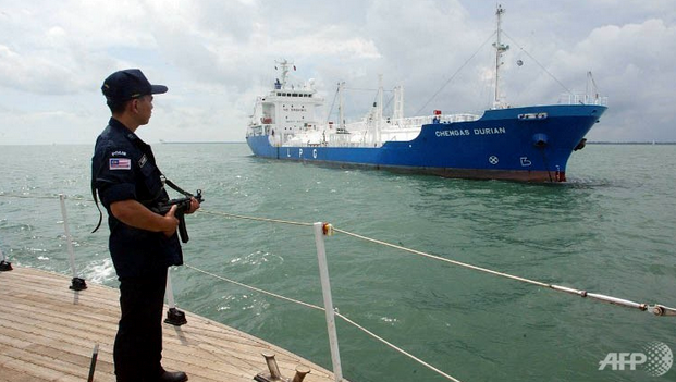 File photo: An armed Malaysian marine policeman standing guard on the deck of his patrol boat while patrolling past a tanker in the Strait of Malacca. Photo credit: AFP
