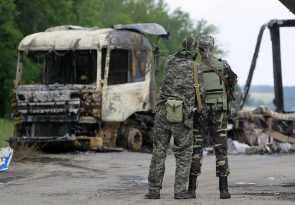 Pro-Russian separatists stand guard at a checkpoint near a burnt truck outside Luhansk, June 18, 2014.