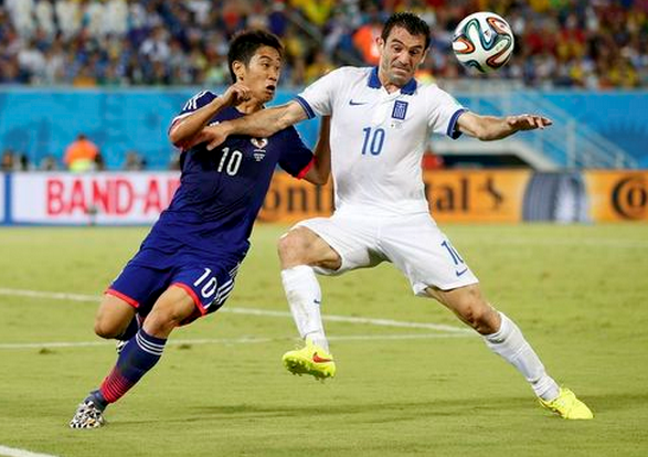 Japan's Shinji Kagawa (L) fights for the ball with Greece's Giorgos Karagounis during their 2014 World Cup Group C soccer match at the Dunas arena in Natal June 19, 2014.