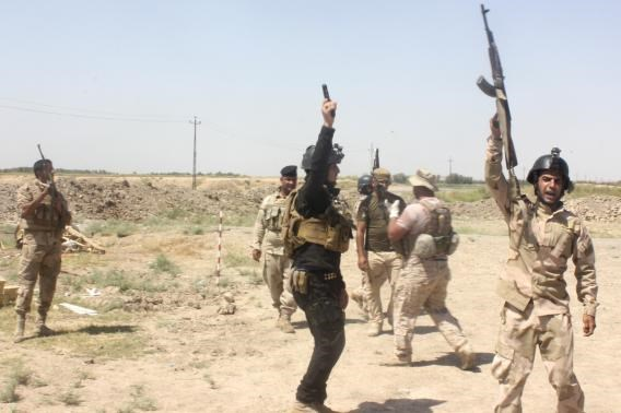 Members of the Iraqi security forces shout slogans as they carry weapons during clashes with Sunni militant group Islamic State of Iraq and the Levant (ISIL) in Muqdadiyah in Diyala province June 19, 2014.
