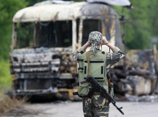A pro-Russian separatist stands guard at a checkpoint near a burnt truck outside Luhansk, June 18, 2014.