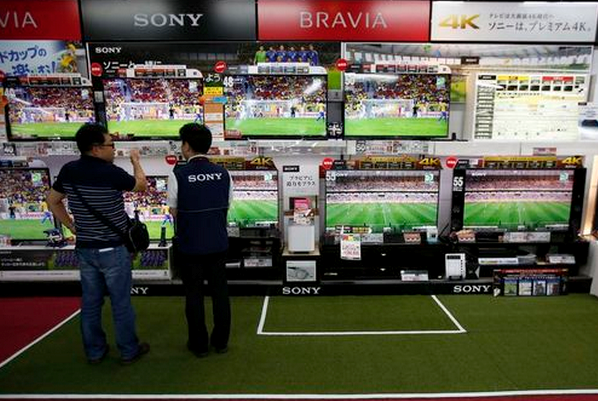 A shopper (L) looks at Sony Corp's Bravia television sets screening a soccer match at an electronics retail store in Tokyo June 10, 2014.
