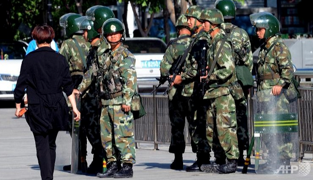 Chinese paramilitary policemen stand guard on a city square in Urumqi in China's Xinjiang region. Photo credit: AFP
