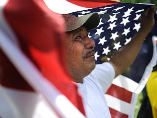 Amilcar Ramirez weeps as he holds a U.S. flag at a May Day rally in Lafayette Square Park near the White House in Washington, May 1, 2010.