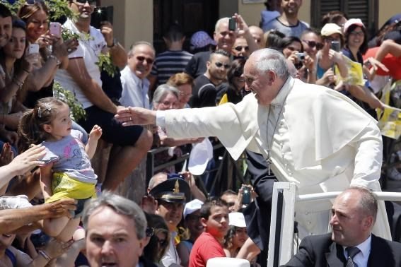 Pope Francis waves to a girl as he arrives to visit the John Paul I seminary in Cassano allo Jonio, southern Italy, June 21, 2014.