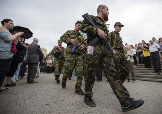 Armed pro-Russian separatists of the self-proclaimed Donetsk People's Republic walk after an oath taking ceremony in the city of Donetsk June 21, 2014.