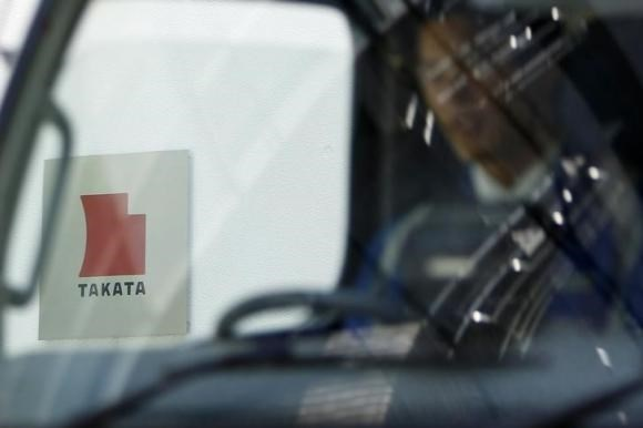 A logo of Takata Corp is seen through a car window outside the company's headquarter building in Tokyo April 12, 2013.