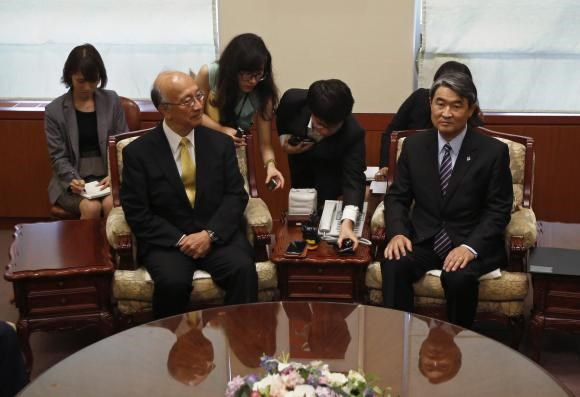 South Korea's Vice Foreign Minister Cho Tae-yong (R) and Japanese Ambassador to South Korea Koro Bessho (L) take their seats before their meeting, after Cho summoned Bessho to deliver a message of protest over the review of the Kono Statement, at the fore