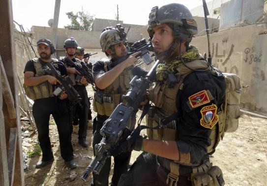 Members of the Iraqi Special Operations Forces (ISOF) take their positions during a patrol looking for militants of the Islamic State of Iraq and the Levant (ISIL), explosives and weapons in a neighbourhood in Ramadi, June 13, 2014. Picture taken June 13,