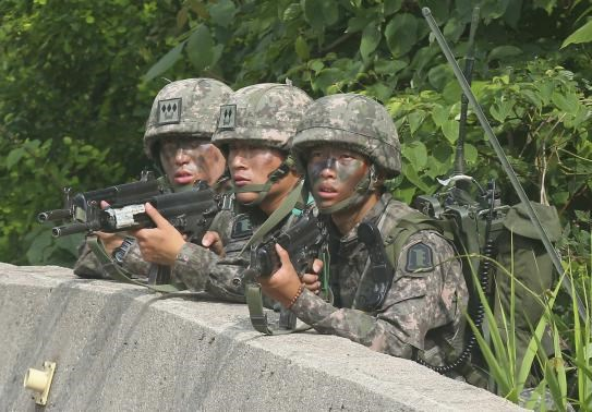 South Korean soldiers take position during a search and arrest operation as troops standoff with a conscript soldier who shot and killed five comrades in Goseong June 23, 2014.