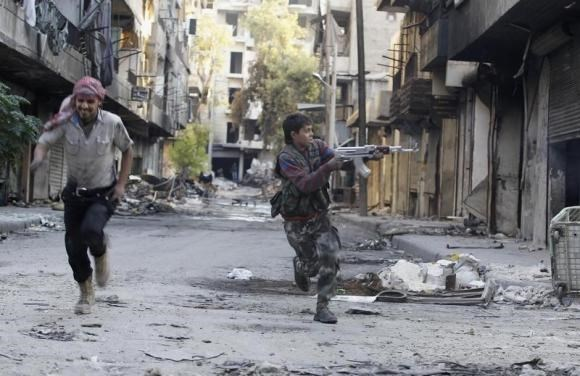 Mohammad (R), a 13 year-old fighter from the Free Syrian Army, aims his weapon as he runs from snipers loyal to the Syrian regime in Aleppo's Bustan al-Basha district October 29, 2013.