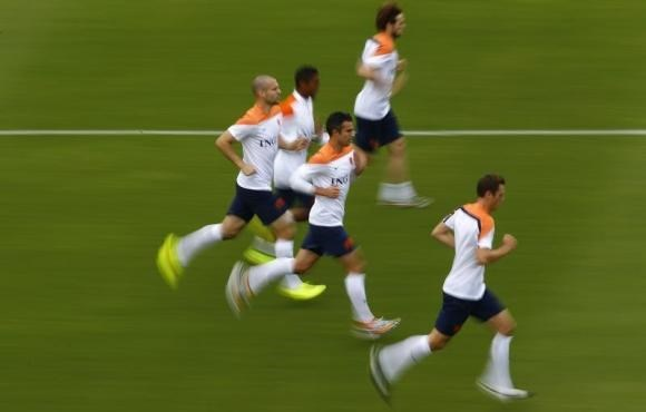 Netherlands' Robin Van Persie (C) and Ron Vlaar (L) run with teammates during a training session in Rio de Janeiro June 19, 2014.