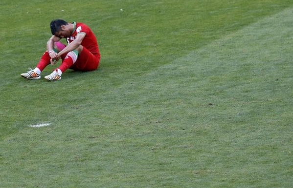 Iran's Amir-Hossein Sadeghi sits on the pitch after their 2014 World Cup Group F soccer match against Argentina at the Mineirao stadium in Belo Horizonte June 21, 2014.